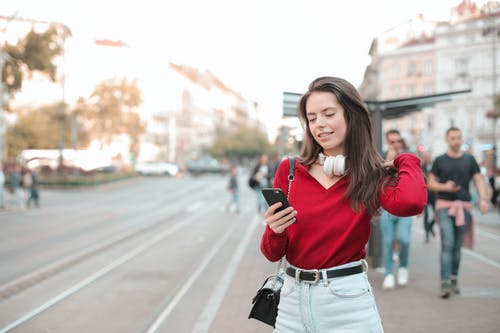 Selective Focus Photo of Woman in Red Sweater and Blue Denim Jeans Using Her Phone While Standing on Sidewalk