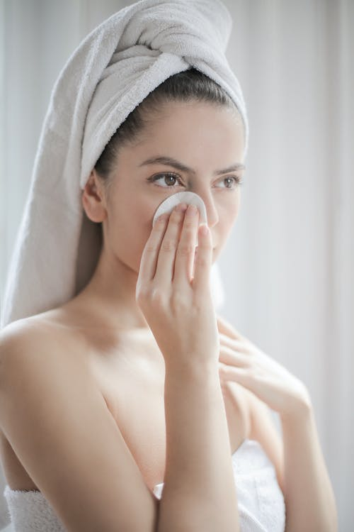 Young female after shower with towel on head using cotton pad while cleaning face