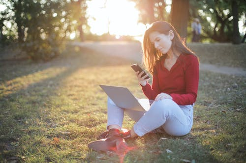 Selective Focus Photo of Woman in a Red Sweater and Blue Pants Sitting on Green Grass Texting While Carrying a Laptop on Her Lap