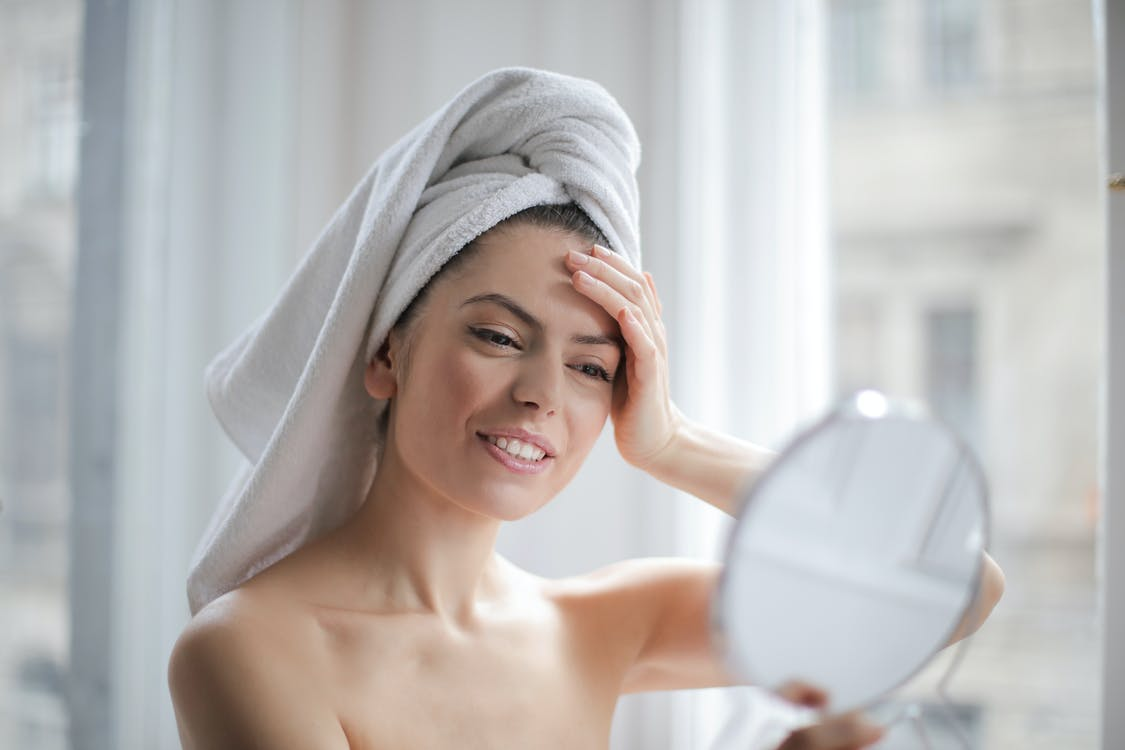 Selective Focus Portrait Photo of Smiling Woman With a Towel on Head Looking in the Mirror