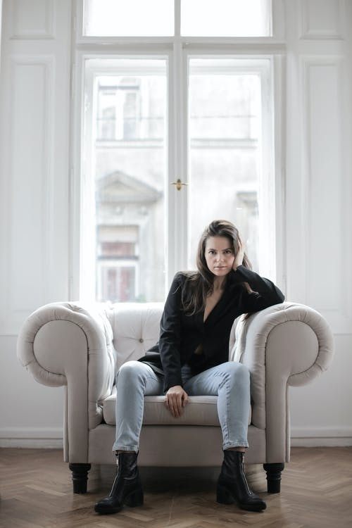 Photo of Woman in Black Coat and Blue Denim Jeans Sitting on White Armchair