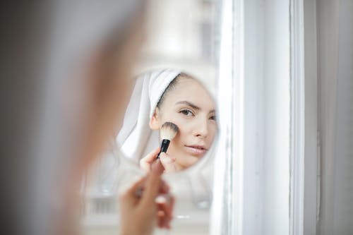 Reflection on mirror of young female using brush on face while applying  makeup