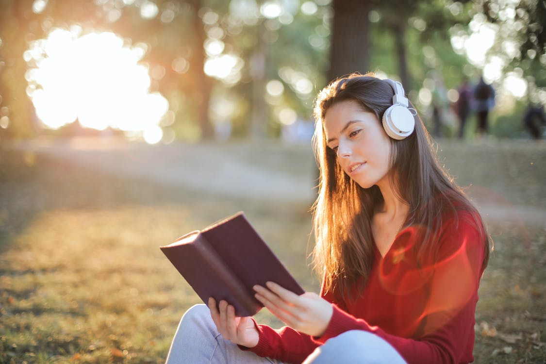 Selective Focus Photo of Smiling Woman in a Red Long Sleeve Top Reading Book While Listening to Music on Headphones