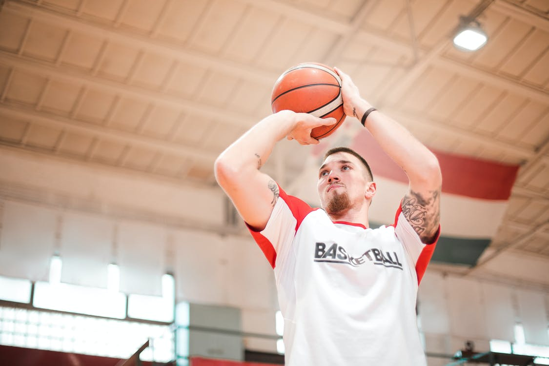 From below of concentrated basketball player with tattoos on arms preparing throwing ball to hoop