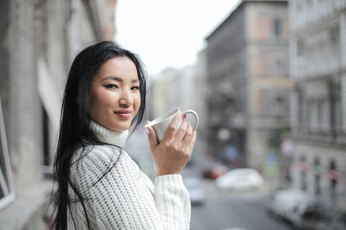 Selective Focus Photo of Woman in White Knit Sweater Holding White Mug