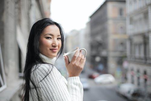 Foto De Enfoque Selectivo De Mujer En Suéter De Punto Blanco Sosteniendo Taza Blanca