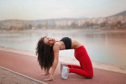 Selective Focus Photo of Woman in Black Sports Bra and Red Leggings Stretching By Body on Water