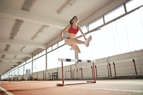 Woman in Red Sports Bra Jumping on White and Black Obstacle