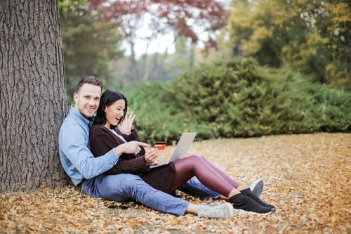 Couple Sitting Near Tree Trunks