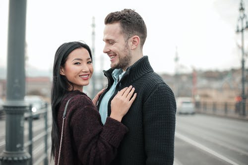Selective Focus Photo of Smiling Couple Standing Next to Each Other