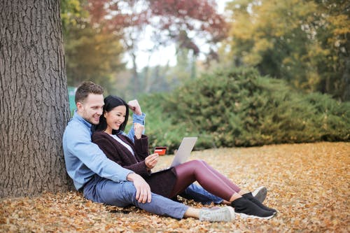 Couple Reclining Beside Tree Trunks