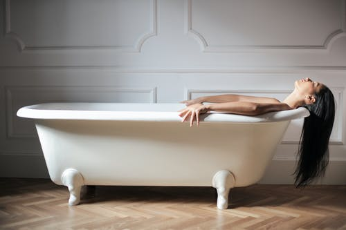 Woman Lying on a White Bathtub