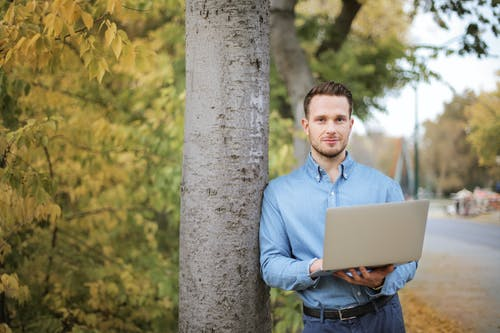 Man in Blue Long Sleeve Holding a Laptop Computer