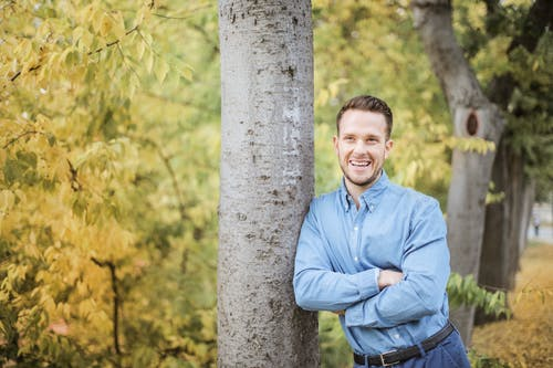 Man in Blue Dress Shirt Standing Beside Tree Trunks