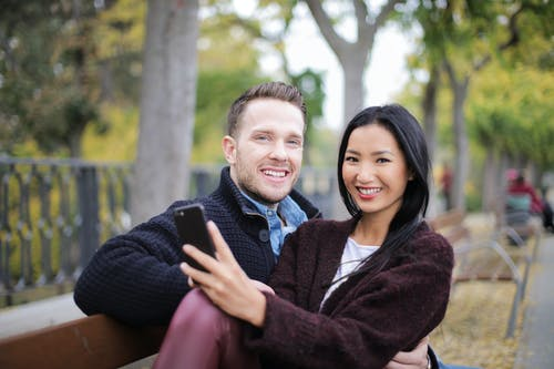 Couple Sitting on Wooden Bench
