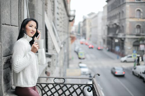 Woman in White Sweater Standing On Balcony