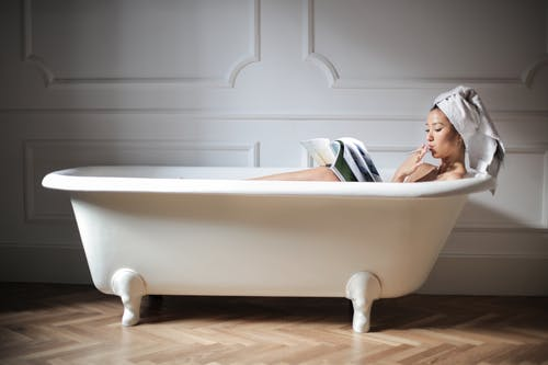 Photo of a Woman in White Bathtub Reading Magazine