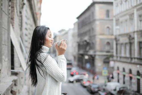 햇빛 아래에서 커피를 마시는 여자