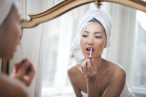 Mujer En Topless Poniendo Lápiz Labial En Los Labios