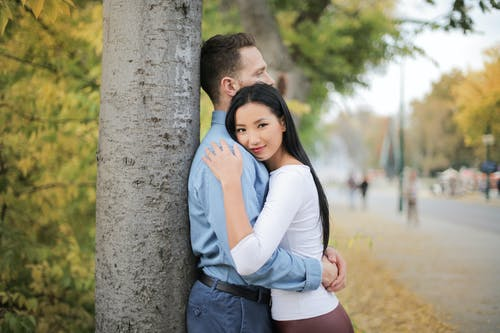 Selective Focus Photo of Hugging Couple Standing Next to a Tree