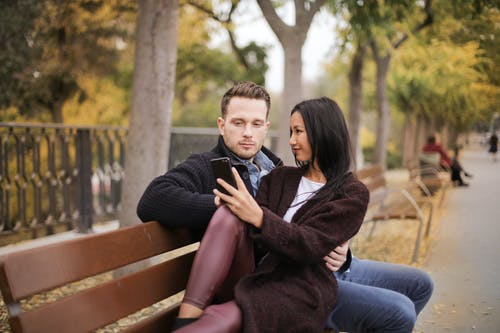 Selective Focus Photo of Couple Sitting on Brown Wooden Bench Looking at a Phone