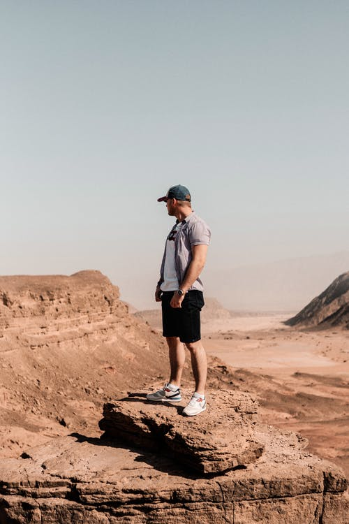 Man Standing On A Brown Rock Formation