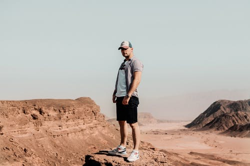 Man Standing on Rock Formation in Desert