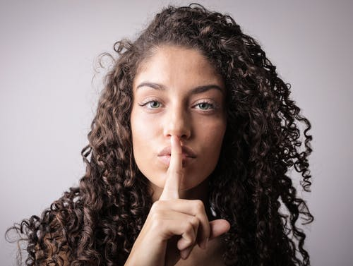 Portrait Photo of Woman with Brown Curly Hair Doing the Shhh Sign