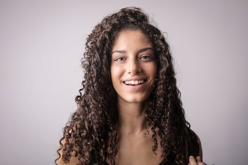 Portrait Photo of Smiling Woman with Brown Curly Hair