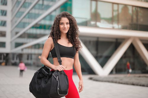 Selective Focus Photo of Smiling Woman In Active Wear Carrying Gym Bag