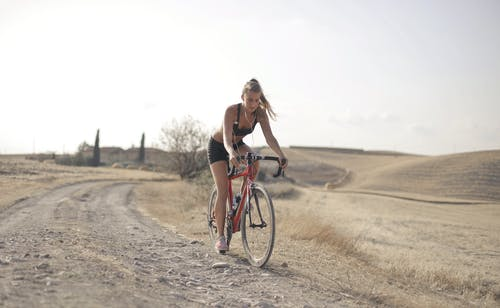 Woman Riding a Red Bicycle on Dirt Road