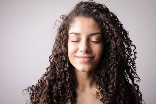 Portrait Photo of Smiling Woman with Brown Curly Hair with Her Eyes Closed