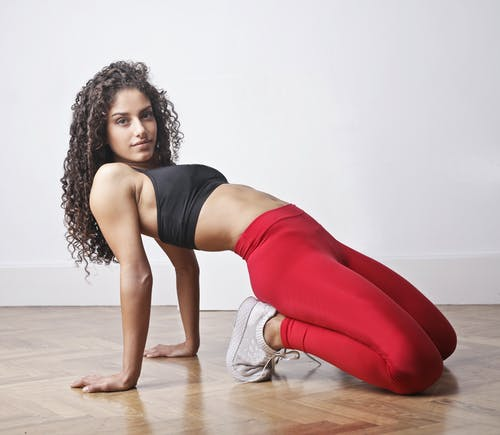 Woman in Black Tank Top and Red Leggings Doing Exercise