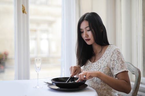 Woman Eating Breakfast Near Glass Window