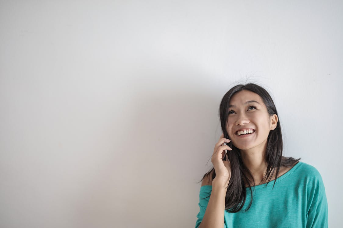 Portrait Photo of Smiling Woman in a Teal Top Talking on the Phone