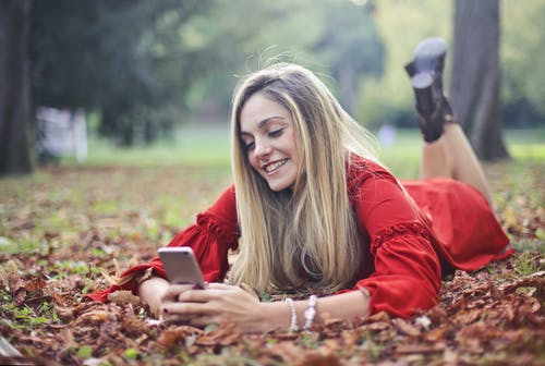 Photo of Smiling Woman in Red Long Sleeve Shirt Lying on Stomach on Dry Leaves While Texting