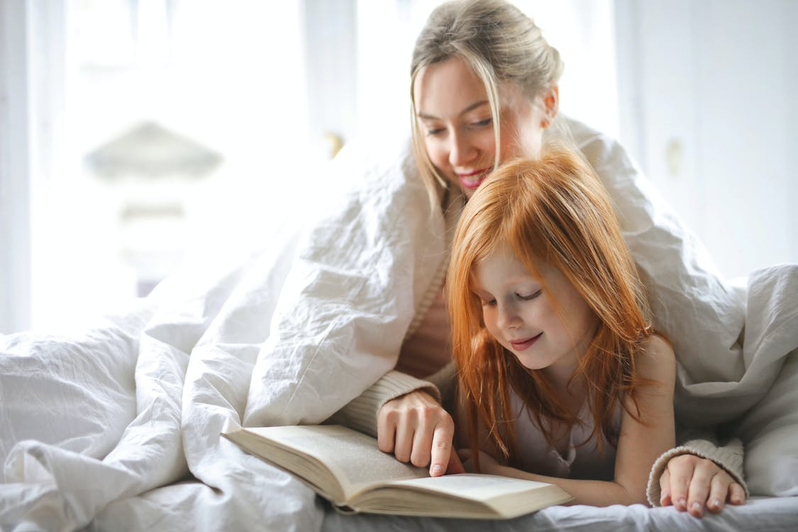 Photo of Mother and Daughter Reading a Book While in Bed