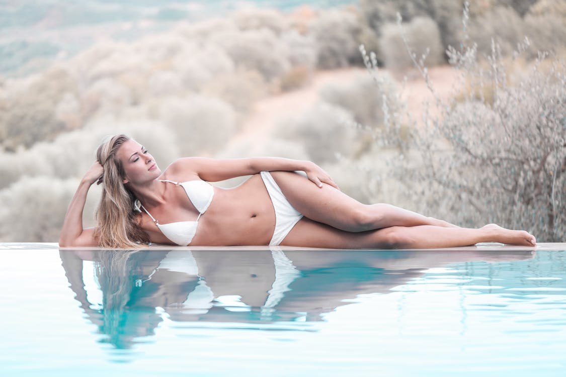 Photo of Woman in White Bikini Lying by Poolside with Her Eyes Closed