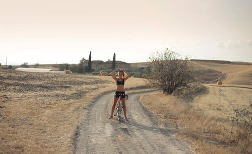Young female in sportswear standing with cycle on road in remote countryside while doing ponytail