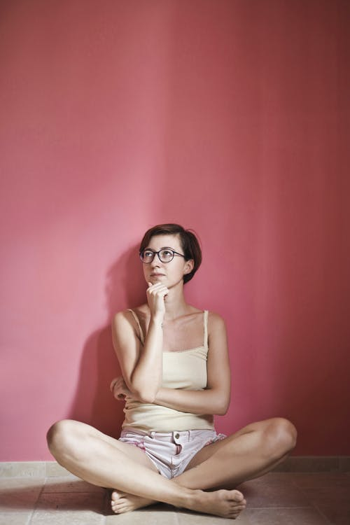 Photo of Thinking Woman in Yellow Tank Top and Pink Shorts Sitting on Floor Next to Pink Wall