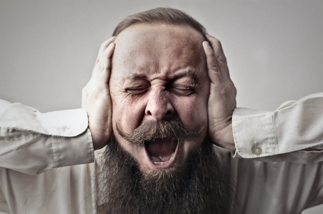 Close-up Photo of Screaming Man With a Full Beard Covering His Ears and Closing His Eyes