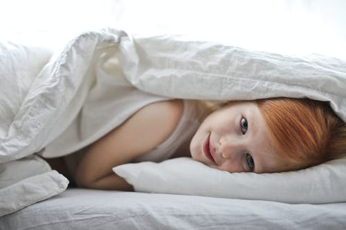 Photo of Young Girl Lying in White Bed