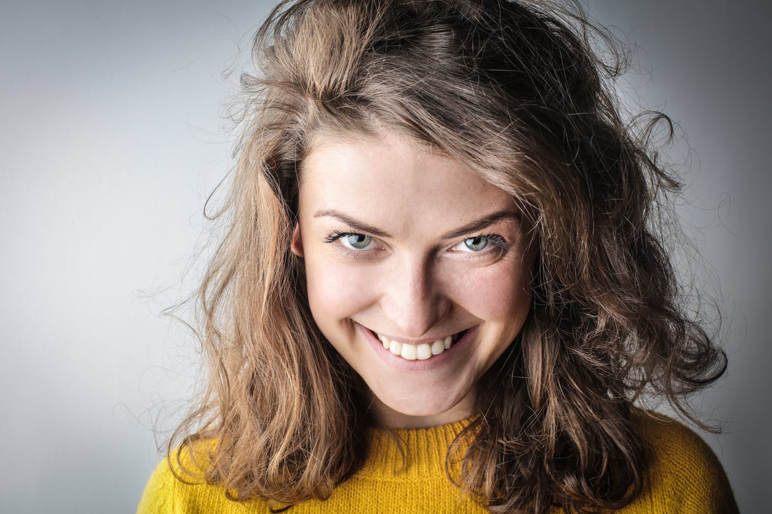 Portrait Photo of Smiling Woman in Yellow Sweater