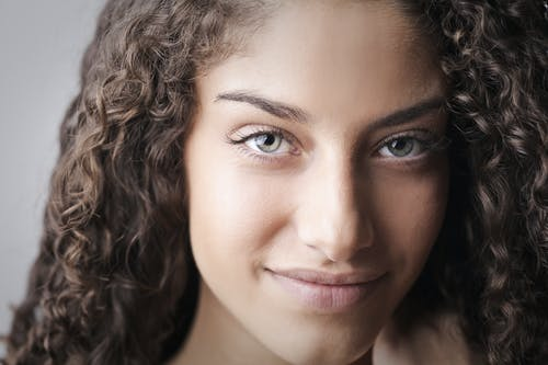 Close-up Portrait Photo of Smiling Woman With Brown Curly Hair