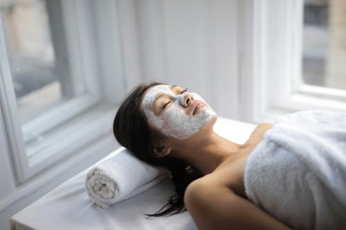 Young Asian woman on towel and with mask on face lying on covered table in light spa salon