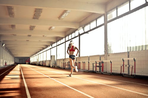 Back View Photo of Woman in Active Wear Running on Track Field