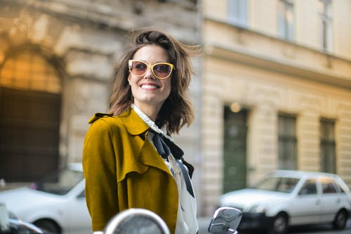 Selective Focus Photo of Smiling Woman in Brown Coat and Sunglasses Looking Away