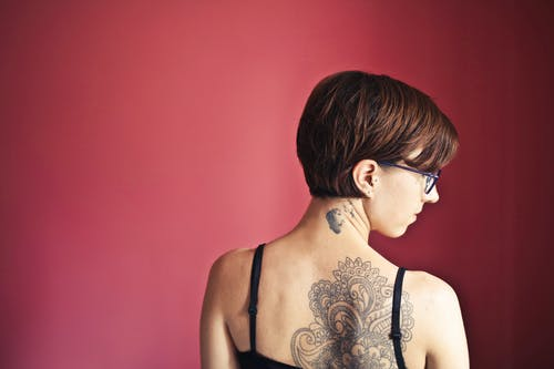 Back View Photo of Woman With a Floral Tattoo on Her Back Standing In Front Of Red Background