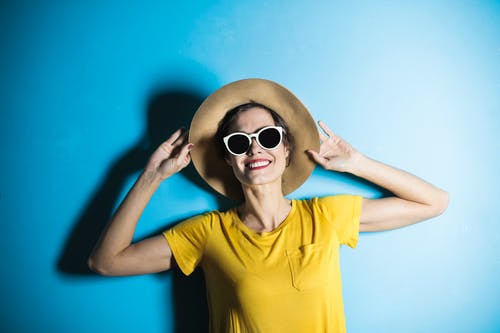 Photo of Smiling Woman in Yellow T-shirt, Sun Hat and White Framed Sunglasses Posing In Front of Blue Background