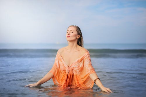 Photo of Woman in Orange Top Standing in Body of  Water with Her Eyes Closed